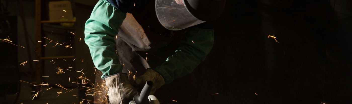 Man grinding down metal with tools, gloves and a facemask - the image is focused on his capabilities working at Oertel Metalworks